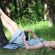 Beautiful girl in dress lying on grass under tree with book and  — Stock Photo #70085335