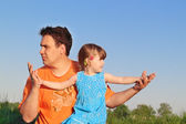 Father and daughter sitting in meadow and look in different dire — Stock Photo