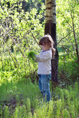 Cute little girl in jeans standing in woods and gather herbs — Stockfoto