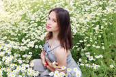 Beautiful girl with clock on hand in dress sits in chamomile flo — Stockfoto