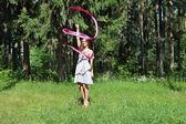Beautiful girl in dress is engaged in rhythmic gymnastics with r — ストック写真