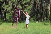 Beautiful girl in dress is engaged in rhythmic gymnastics with r — Stock Photo