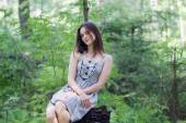 Beautiful girl in dress sitting on stump in forest and looking a — Foto de Stock