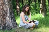 Beautiful girl in dress sitting under tree on grass and reading  — Foto de Stock