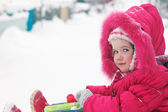 Little girl in red warm clothes smiles and looks at camera at wi — Stock fotografie