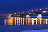 Bridge with lanterns and reflection in water of river with ice a — Стоковое фото