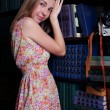 Beautiful girl with blond hair is standing next to shelves of bo — Stock Photo #71331077