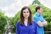 Smiling young woman in blue in summer park and man stands behind — Stock Photo