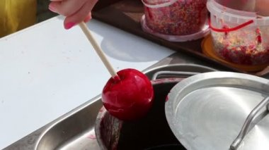 Female hand turns red sweet apple on stick in syrup — Stock video