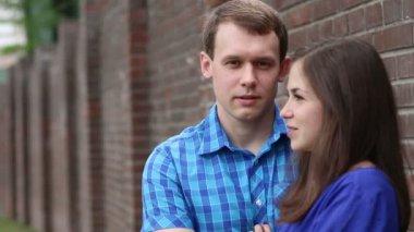 Glückliche Frau und junger Mann stehen in der Nähe von Mauer und Talk. Mann im Fokus — Stockvideo