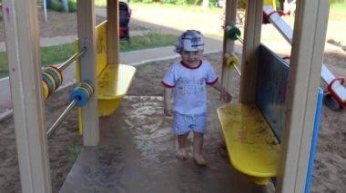Gelukkig weinig knappe jongen zit op de Bank op speelplaats in de zomer — Stockvideo