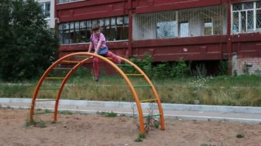 Little girl sits on semicircular ladder and waves hand at playground — Stock Video