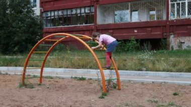 Little girl climbs on semicircular ladder at playground — Stock Video