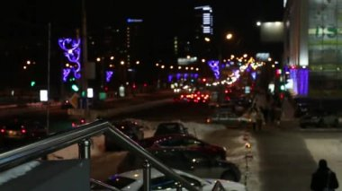 Moving cars, walking people and buildings with illumination at night city out of focus. Time lapse — Stock Video