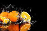オレンジ色の果実と水しぶき水 — ストック写真