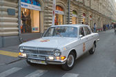 "Soviet white retro car GAZ-24 ""Volga"" retro rally Gorkyclassic in motion around the Gum, Moscow — Stockfoto"