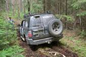 """Off-road vehicle Toyota Land Cruiser on a forest road, rear view, 3rd international meeting """"Motors of war"""" near the town of Chernogolovka, Moscow region — Stockfoto"""
