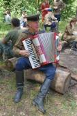 """Accordionist playing the accordion at the bus stop to rest in the forest, 3rd international meeting """"Motors of war"""" near the city Chernogolovka, Moscow region — Stock Photo"""
