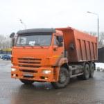 Orange dump truck KAMAZ on snow-melting point, Moscow — Stock Photo #64994651