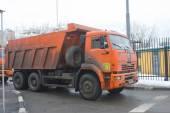 Orange dump truck KAMAZ enters into a snow-melting point Moscow — Stock Photo