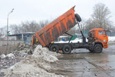 The discharge of snow from the body of the orange truck in negotable on snow-melting point, Moscow — Stock Photo
