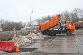 Orange dump truck KAMAZ about negotable on snow-melting point, Moscow — Stock Photo