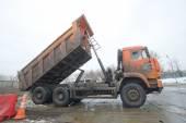 Orange dump truck KAMAZ pours snow in negotable on snow-melting point, Moscow — Stock Photo