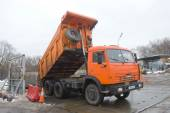 Orange dump truck KAMAZ - 65115 about negotable on snow-melting point, Moscow — Stock Photo