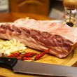 Fresh pork ribs, meat marinated and prepared for roast with garlic. Laying on a wooden table on a round cutting board with knife, chilly peppers and garlic. — Stock Photo #64770561