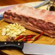 Fresh pork ribs, meat marinated and prepared for roast with garlic. Laying on a wooden table on a round cutting board with knife, chilly peppers and garlic. — Stock Photo #64770821