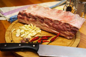 Fresh pork ribs, meat marinated and prepared for roast with garlic. Laying on a wooden table on a round cutting board with knife, chilly peppers and garlic. — Stock Photo