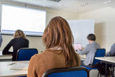 People sitting rear at the desks in the education class — Stock Photo