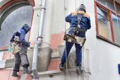 Bricklayer working on the high building. Building maintenance: two men working at height. — Stock Photo