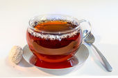 Transparent cup of black tea and spoon, on a white background — Stock Photo