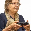 Happy senior woman in glasses playing video games with gamepad — Stock Photo #69526507