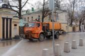 MOSCOW, RUSSIA - APRIL 7, 2015: Red KAMAZ 53605 watering and cleaning machines at the city street. — ストック写真