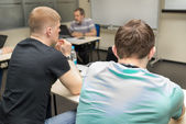 Two students sitting rear in the classroom at the dest and coach sitting near the whiteboard in blur — Stok fotoğraf