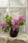 Lush bouquet of lilac in a brown clay vase on a window sill — Stock Photo