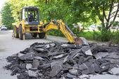 Yellow modern excavator removes the debris the asphalt road in city — Stock Photo