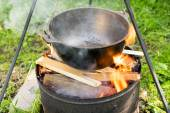 Cooking in a metal pan in a campfire — Stock Photo