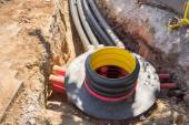 Excavation pit, electrical cables and optical fibres in the digging on a construction site — Stock Photo