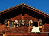 Facade of a old farmhouse and big cow bells — Stock Photo