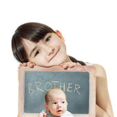 Caucasian child sister holding chalkboard and baby brother face isolated — Stock Photo