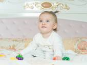 Small caucasian child girl play with toys on the bed at home — Stock Photo