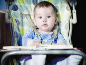 Small caucasian baby boy sitting in chear with notepad — Stockfoto