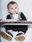Small caucasian baby boy sitting in chear with notepad — Stock Photo