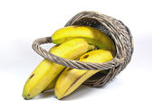 Four Yellow Bananas in an Upturned Wicker Basket — Stock Photo