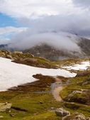 Stony snowy autumn meadows of high Alpine mountains. Dark peaks touch heavy misty clouds. Cold and damp end of the day in Alps mountains — Stock Photo
