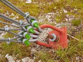 Twisted iron rope end in crews crome glittering snap hooks. Detail of thin strong rope end anchored at rock, climbers equipment — Stock Photo
