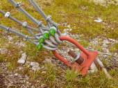 Detail of strong sing and scrap in green yard, iron twisted rope fixed by screws snap hooks and grommets at anchor in ground. — Stock Photo